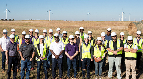 Students in hard hats and vests with windmills